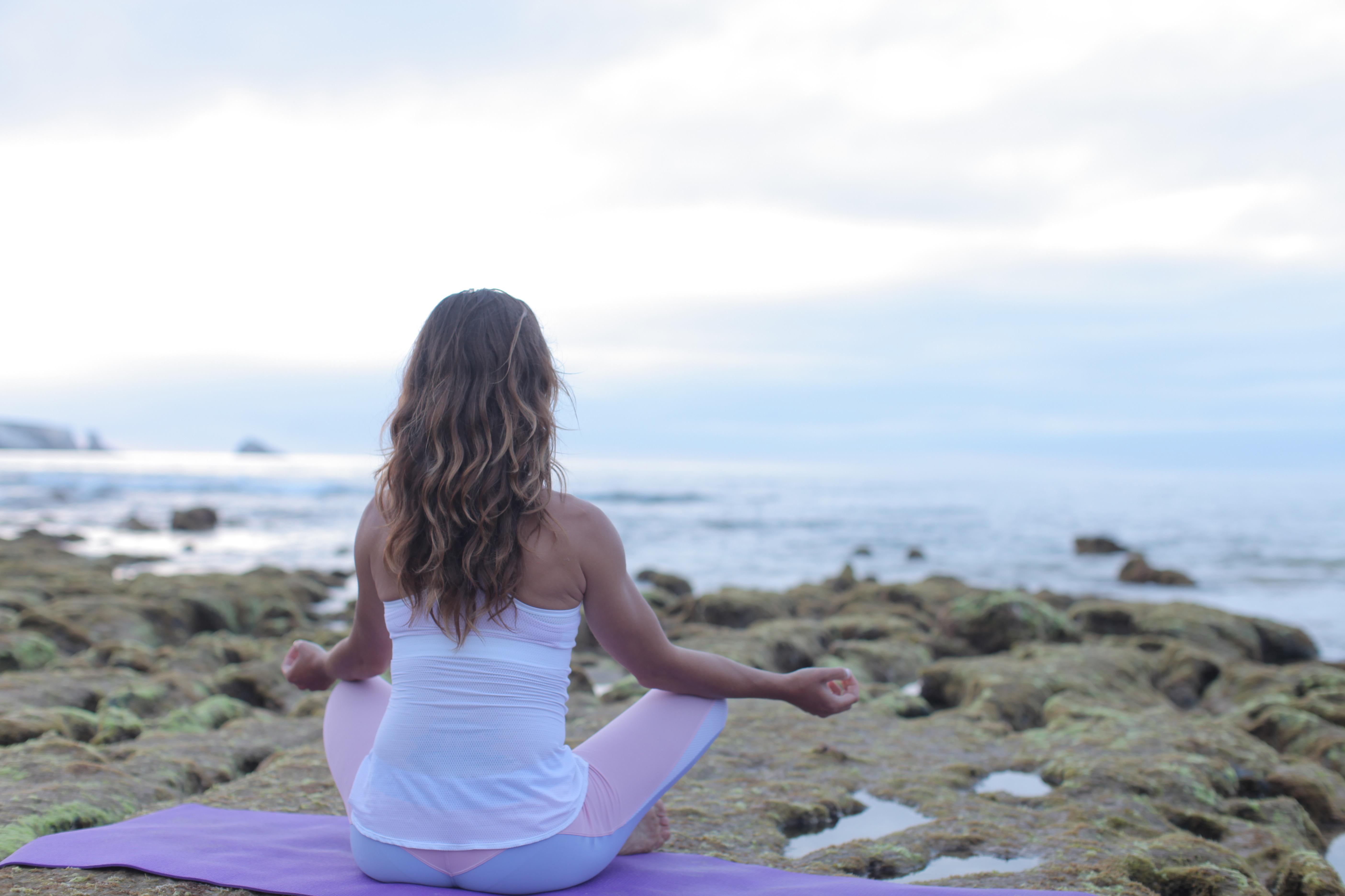 水辺で瞑想する女性